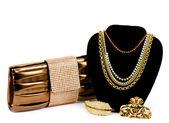 Fashionable handbag and golden jewelry on white background. — Stock Photo