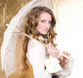 Blond woman with vintage umbrella on golden — Stock Photo
