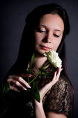 Beautiful young woman with white rose on background — Stock Photo
