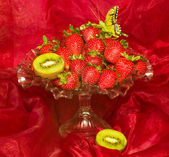 Red fresh strawberry in vase on red background — Stock Photo