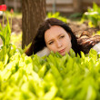 Beautiful woman in spring green lilies of the valley — Stock Photo