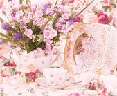 Vintage teacups, ballet dancer statuette and flowers — Stock Photo