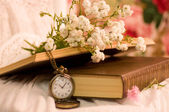 Beautiful flowers, books and antique clock — Stock Photo