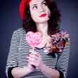 Frenchwoman with pink spiral lollipops — Stock Photo