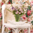 Vase with flowers and female cloth on white chair — Stock Photo