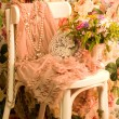 Vintage elegant dress, cup and flowers on white chair - Stock Photo