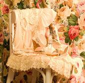 Vintage elegant dress and perfume bottles on white chair — Stock Photo