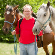 Handsome smiling man with horse in the forest — Stock Photo