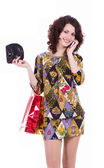 Young woman with shopping bags talking on cell phone — Stock Photo