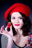 Young woman with strawberry in red beret — Stock Photo