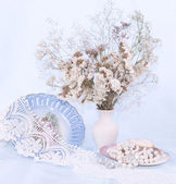 Beautiful flowers, vintage plate and beads — Stock Photo
