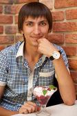 Junger mann sitzt im café mit kirsche eis — Stockfoto