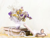 Beautiful spring flowers in a vase with banner add and book — Stock Photo