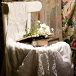 Flowers, books, clock and female cloth on white chair - Stock Photo