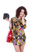 Young woman with shopping bags talking on cell phone on a white background — Stock Photo