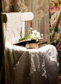 Flowers, books, clock and female cloth on white chair — Stock Photo