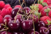Berry mix pozadí - maliny, moruše, jahody a třešně — Stock fotografie