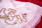 Biżuteria złota i białe koronki na czerwonym tle — Zdjęcie stockowe