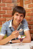Young man sitting at cafe with cherry ice cream — Stock Photo