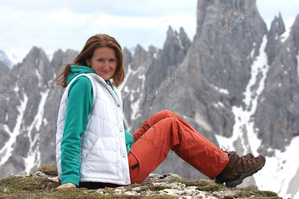 Sitting smiling girl with the high rocky mountains at the background — Stock Photo #11294829