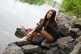 Sexy young girl on the stone banks of the River — Stock Photo