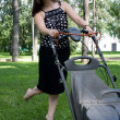 Girl with a lawn mower — 图库照片