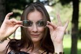 Retrato de mujer de negocios probándose gafas de sol — Foto de Stock