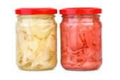 Glass jars with white and pink marinated sliced ginger roots — Stock Photo