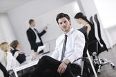 Handsome young business man with colleagues in background — Stock Photo