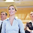 Business woman standing with her staff at conference - Stock Photo