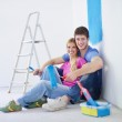 Happy young cople relaxing after painting in new home — Stock Photo