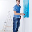 Handsome young man paint white wall in color — Stock Photo #11270818