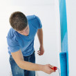 Handsome young man paint white wall in color — Stock Photo #11270819