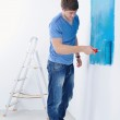 Handsome young man paint white wall in color — Stock Photo #11270824