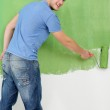 Handsome young man paint white wall in color — Stock Photo #11270836