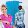 Happy couple paint wall at new home — Foto de Stock
