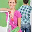 Happy couple paint wall at new home — Stockfoto