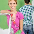 Stock Photo: Happy couple paint wall at new home