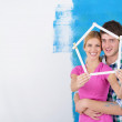Happy couple paint wall at new home — Stok fotoğraf