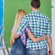 Happy couple paint wall at new home — Stock Photo