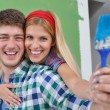 Happy couple paint wall at new home — Stock Photo #11276332