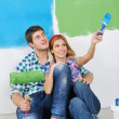 Happy couple paint wall at new home - Stok fotoğraf
