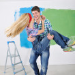 Happy couple paint wall at new home - Stock Photo
