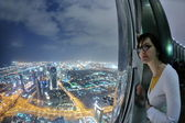 Beautiful woman portrait with big city at night in background — Stock Photo