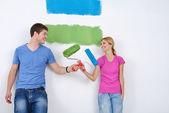 幸せなカップルの新しい家で壁のペンキ塗り — ストック写真