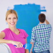Happy couple paint wall at new home — Stock Photo #11465966