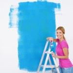 Постер, плакат: Happy smiling woman painting interior of house