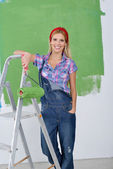 Happy smiling woman painting interior of house — Stock Photo