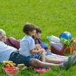 Happy family playing together in a picnic outdoors - Foto Stock