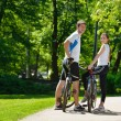 Happy couple riding bicycle outdoors — Foto Stock